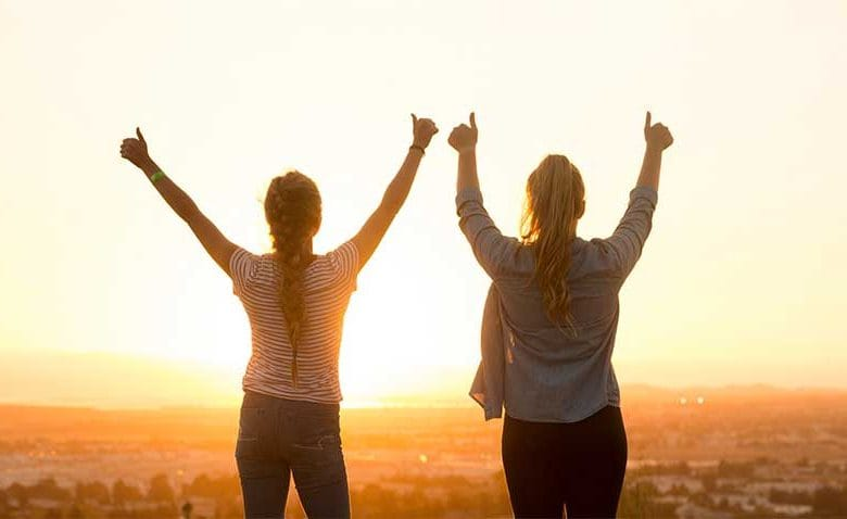 two girl friends infront of sunset