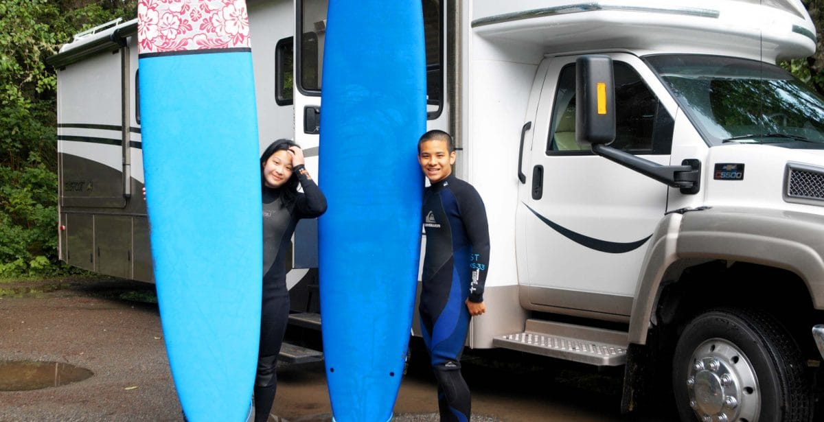 Kids with surfboards in front of an rv