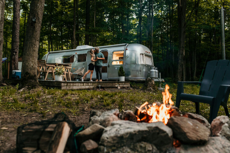 couple by airstream in front of campfire
