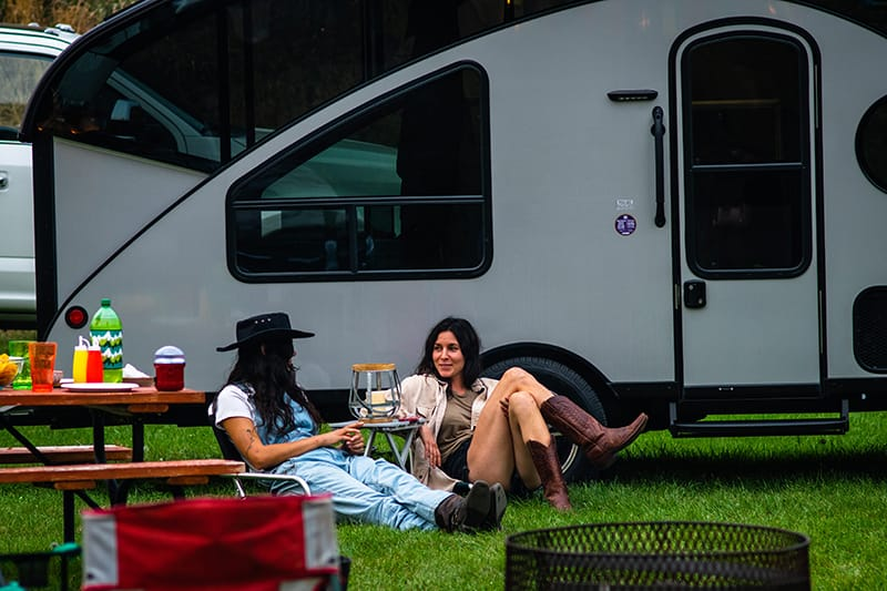 two ladies lounging in front of rv