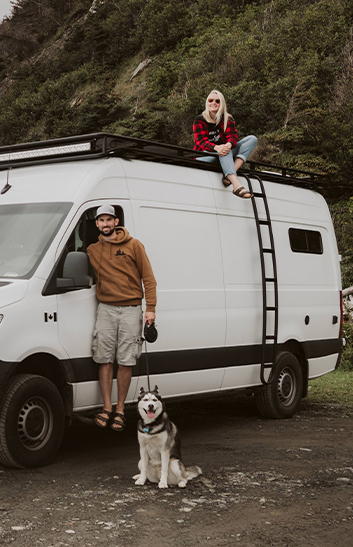 couple posing with dog in front of an RV